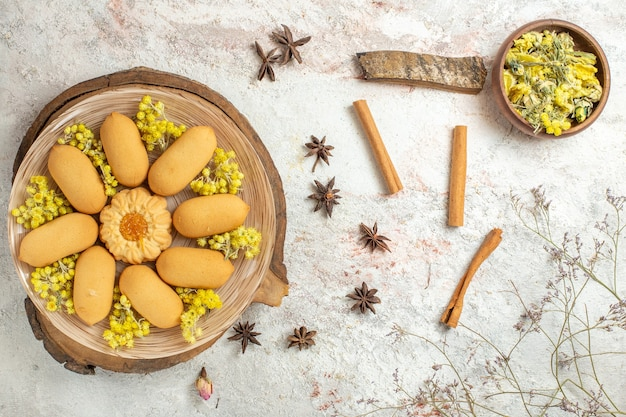 Talerz ciastek na drewnianym talerzu i różne suszone zioła wokół niego na marmurze