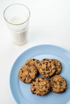 Talerz ciastek z kawałkami czekolady i szklanka mleka