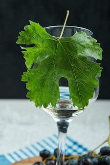 Talerz czarnych winogron i kieliszek wina z liściem na białym stole, z bliska