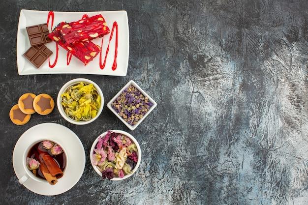 Talerz czekoladek z suchymi kwiatami i filiżanką ziołowej herbaty i ciastek na szarym podłożu