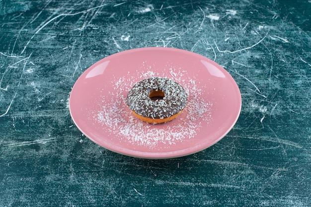 Talerz czekoladowych pączków na niebieskim stole.
