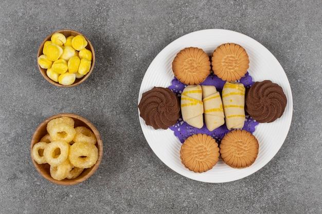 Talerz deserów i cukierków na marmurze.