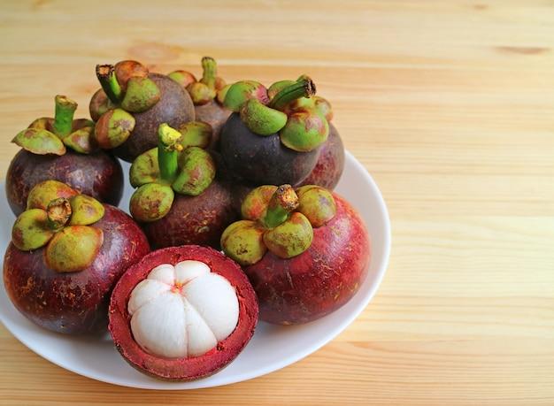 Talerz dojrzałych całych owoców mangostanu z jednym przekrojem na pół na drewnianym stole