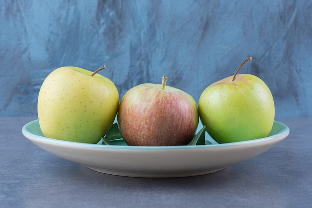 Talerz dojrzałych jabłek i liści na ciemnej powierzchni