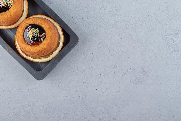 Talerz dwóch mini ciastek z galaretką ułożony na wierzchu plasterka pomarańczy