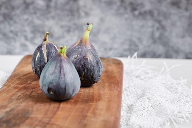 Talerz fioletowych fig na marmurze.