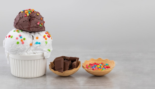 Talerz gałki lodów waniliowych i czekoladowych swith posypuje kawałki czekolady i rożki waflowe.