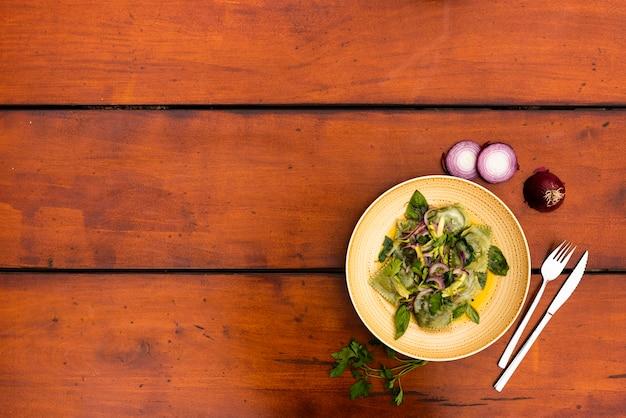 Talerz garnirunku zielony pierożka makaron z cebulą na drewnianym stole