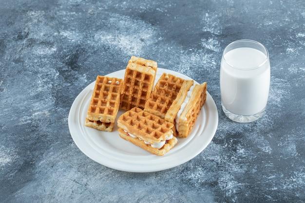 Talerz gofrów i szklankę mleka na marmurowej powierzchni.