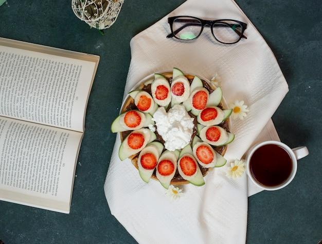 Talerz gofrów z owocami i lodami oraz filiżanka herbaty. widok z góry.