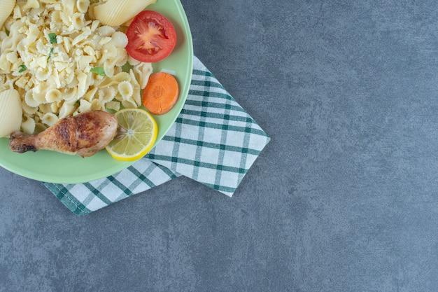 Talerz gotowanego makaronu i podudzie z kurczaka na kamiennej powierzchni.