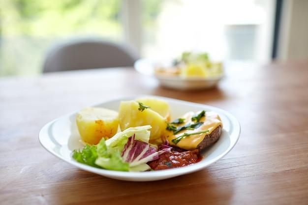 Talerz gotowanych ziemniaków z zieloną sałatą warzywną i kotletem na drewnianym stole