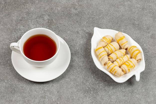 Talerz herbatników i filiżankę herbaty na powierzchni marmuru