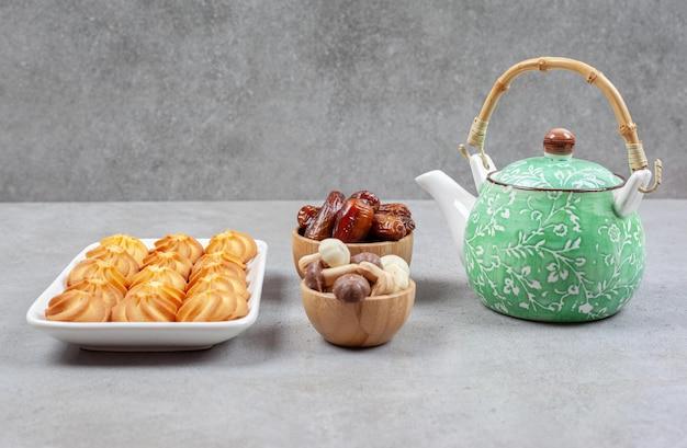 Talerz herbatników obok kwiecisty czajniczek i miski z daktylami i grzybowymi czekoladkami na marmurowej powierzchni.