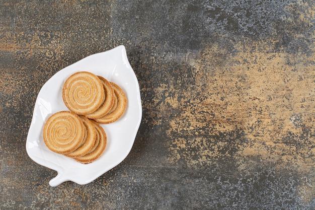 Talerz herbatników sezamu na marmurowym stole.