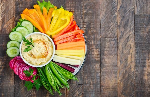 Talerz hummus z różnorodnymi przekąskami warzywnymi. zdrowe wegańskie i wegetariańskie jedzenie. widok z góry, leżał płasko, miejsce.