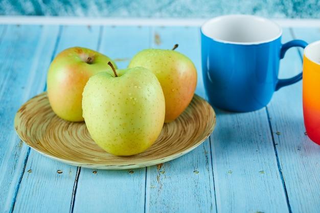 Talerz jabłkowy i dwa kolorowe kubki na niebieskim stole.