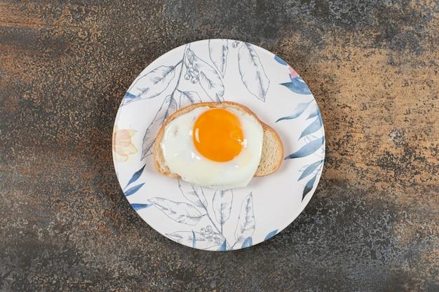 Talerz jajek na kromce białego chleba.