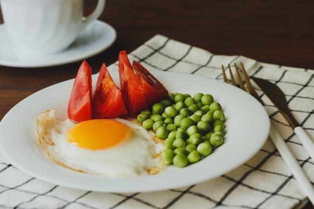 Talerz jajek sadzonych z warzywami na drewnianym stole