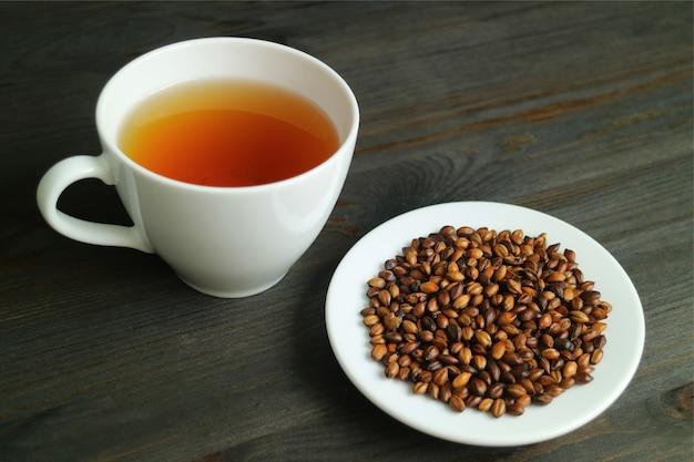 Talerz jęczmienia palonego z filiżanką gorącej japońskiej herbaty jęczmiennej lub mugicha na drewnianym stole