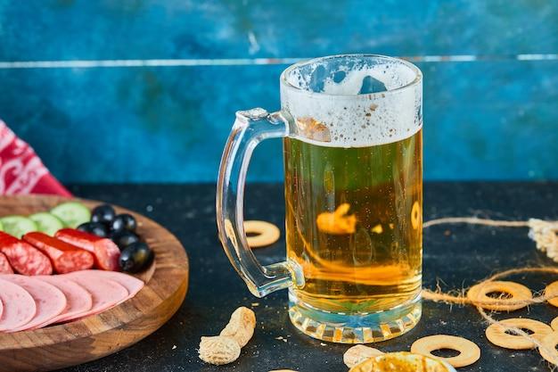 Talerz kiełbasek i kufel piwa na ciemnym stole.