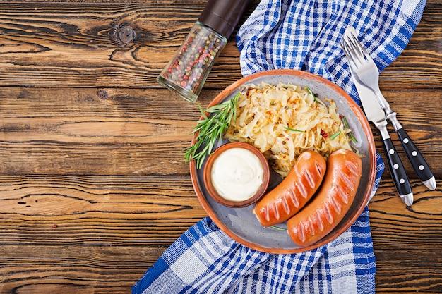 Talerz kiełbasy i kapusta kiszona na drewnianym stole. tradycyjne menu oktoberfest. leżał płasko. widok z góry.
