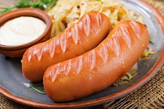 Talerz kiełbasy i kapusta kiszona na drewnianym stole. tradycyjne menu oktoberfest