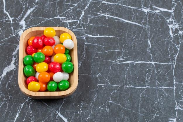 Talerz kolorowych cukierków na tle marmuru.