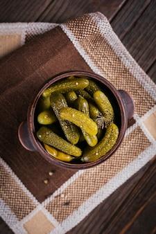 Talerz korniszonów, ogórki kiszone na rustykalnej powierzchni drewnianej. czyste jedzenie, koncepcja żywności wegetariańskiej. widok z góry