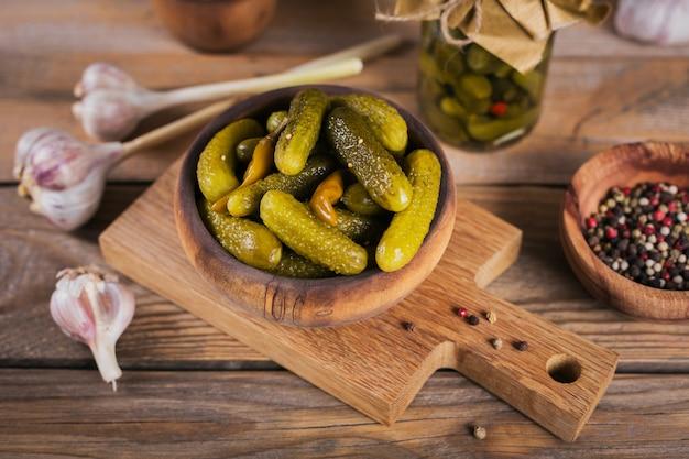 Talerz korniszonów, ogórki kiszone na rustykalnym drewnianym stole. czyste jedzenie, koncepcja żywności wegetariańskiej