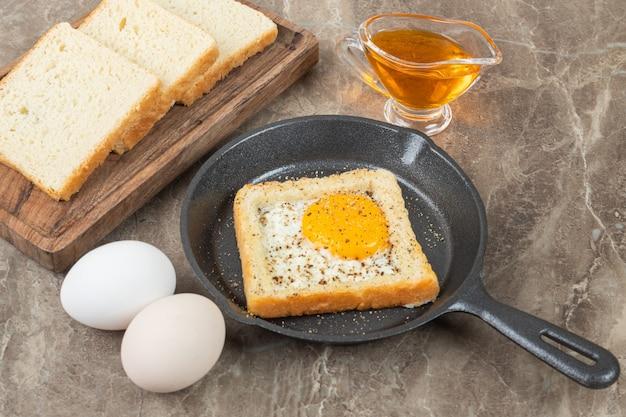Talerz kromki pełnoziarnistego chleba z jajkiem sadzonym i przyprawami.