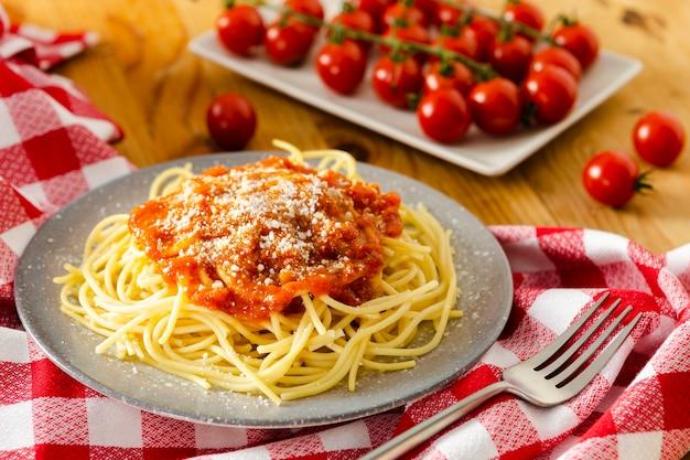 Talerz makaronu z pomidorami na obrusie