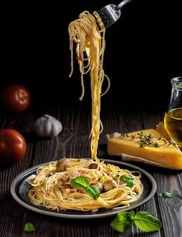 Talerz makaronu z serem, pieczarkami i warzywami, na ciemnym drewnianym stole