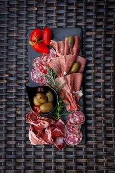 Talerz mięsny z oliwkami, chili na tle łozinowego stołu.