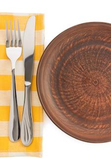 Talerz, nóż i widelec na serwetce na białym tle