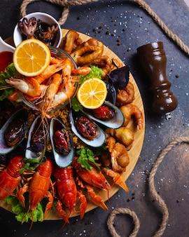 Talerz owoców morza z krewetkami, małżami, homarami podawany z cytryną