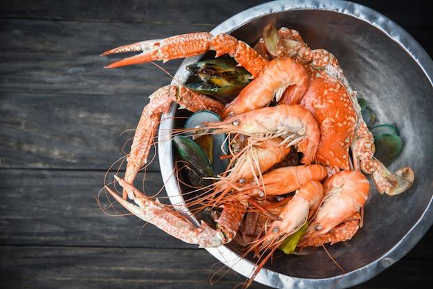 Talerz owoców morza ze skorupiakami z parującymi krewetkami krewetkowymi małżami gotowanymi w gorącym garnku z ziołami i przyprawami