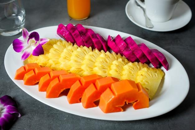 Talerz owocowy, ananas, papaja, na czarnym tle