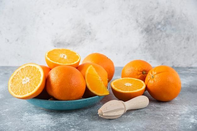 Talerz pełen pokrojonych w plasterki i całych soczystych pomarańczy z drewnianym rozwiertakiem.