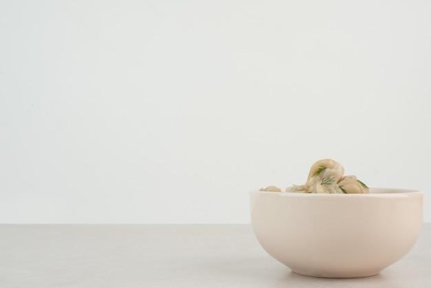 Talerz pierogi z zieleniną na białym stole.