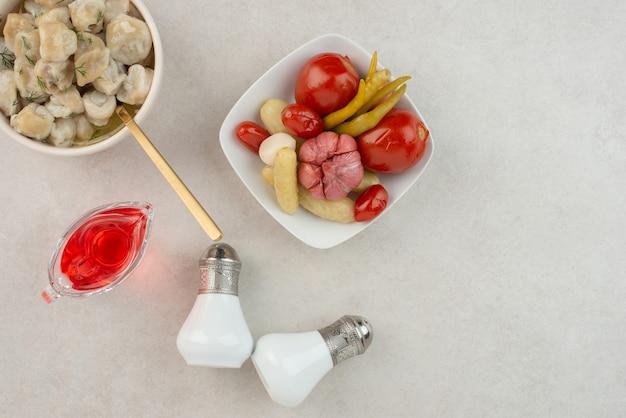 Talerz pierogów z solonymi pomidorami i ogórkami