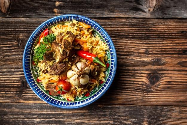 Talerz pilaw z orientalnym ornamentem, drewniane tło, koncepcja orientalnej kuchni uzbeckiej, widok z góry, miejsce na kopię.