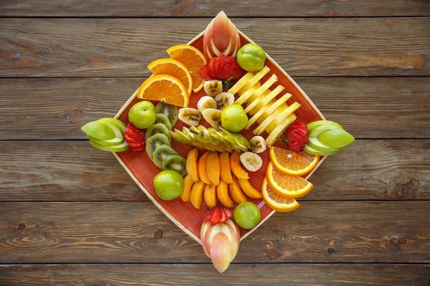 Talerz plasterków owoców z jabłkiem, pomarańczą, truskawką