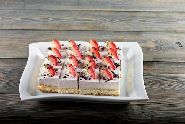 Talerz podawany z deserowym słodkim sufletem, ozdobiony plastrami truskawek