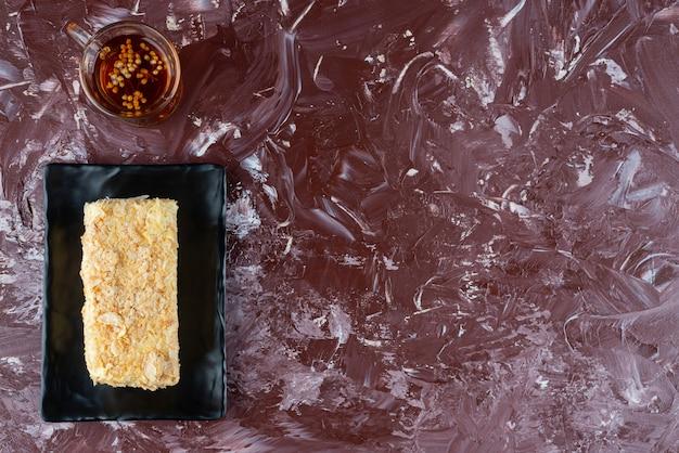 Talerz pokrojone ciasto i szklankę herbaty na tle bordowym.