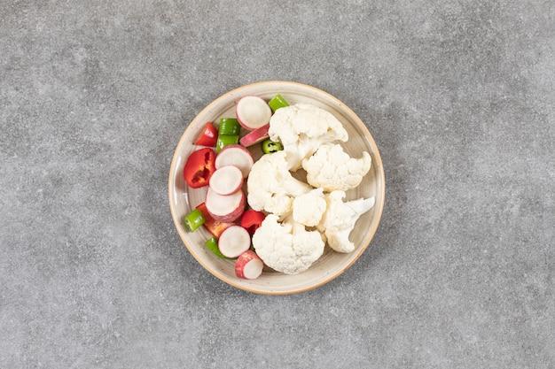 Talerz pokrojone sałatki ze świeżych warzyw na powierzchni kamienia.