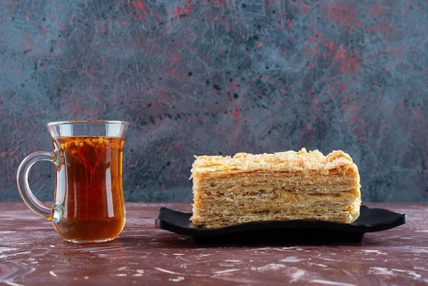 Talerz pokrojonego ciasta i szklankę herbaty na bordowej powierzchni.