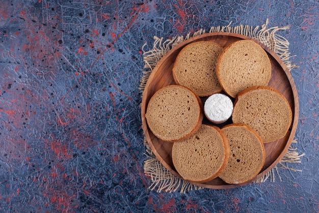 Talerz pokrojony czarny chleb żytni i śmietana na niebieskiej powierzchni.
