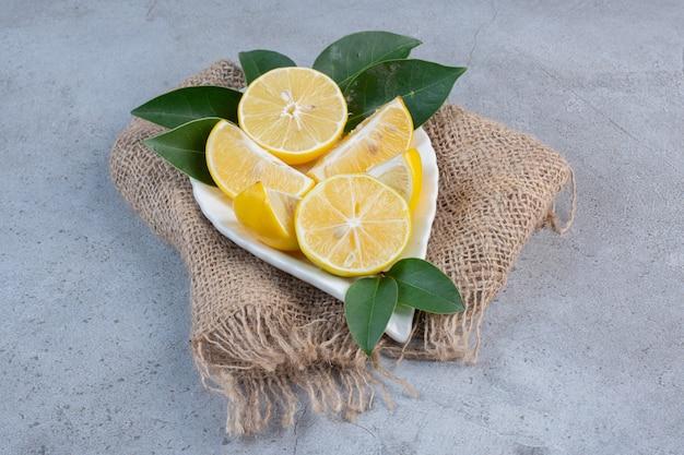 Talerz pokrojonych cytryn na kawałku tkaniny na tle marmuru.