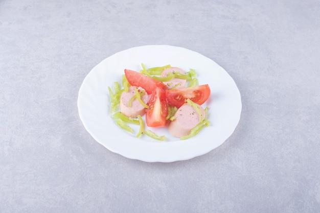 Talerz pokrojonych kiełbasek i pomidorów na tle kamienia.